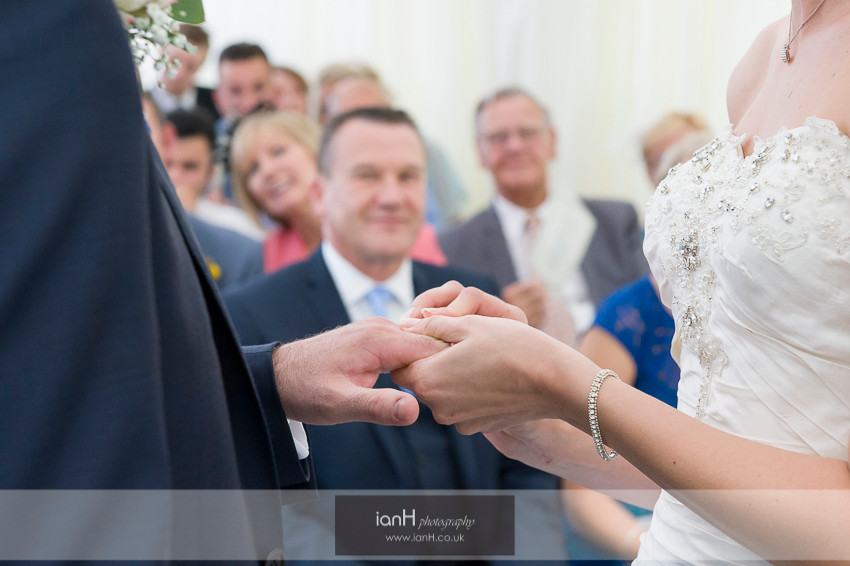 Parents watch as Bride puts ring on her husband's finger