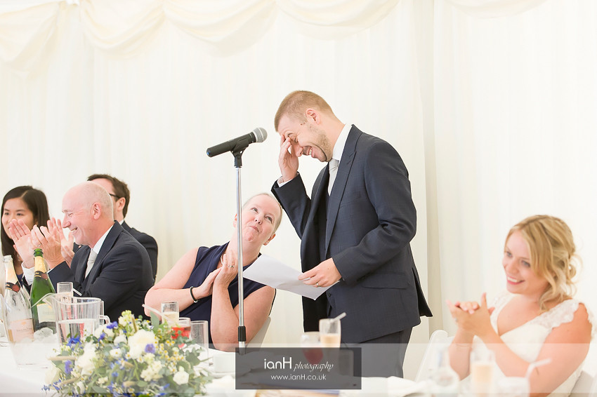 Groom laughing during his wedding speech