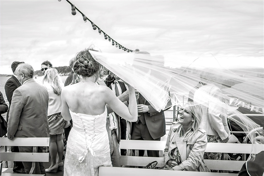 Wind catches the Bride's veil and a woman laughs. Black and white photograph
