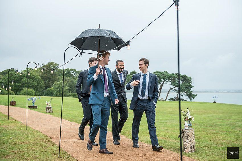 guys arriving with umbrellas at rainy wedding