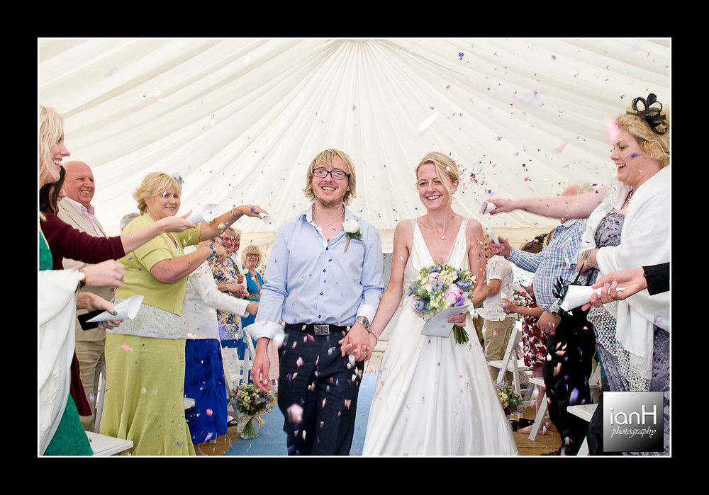 family-throw-confetti-as-couple-walk-down-the-aisle-at-bournemouth-beach-wedding-anniversary