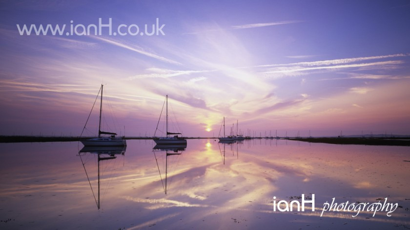 Yachts reflected in the glow of sunrise at Keyhaven in Hampshire