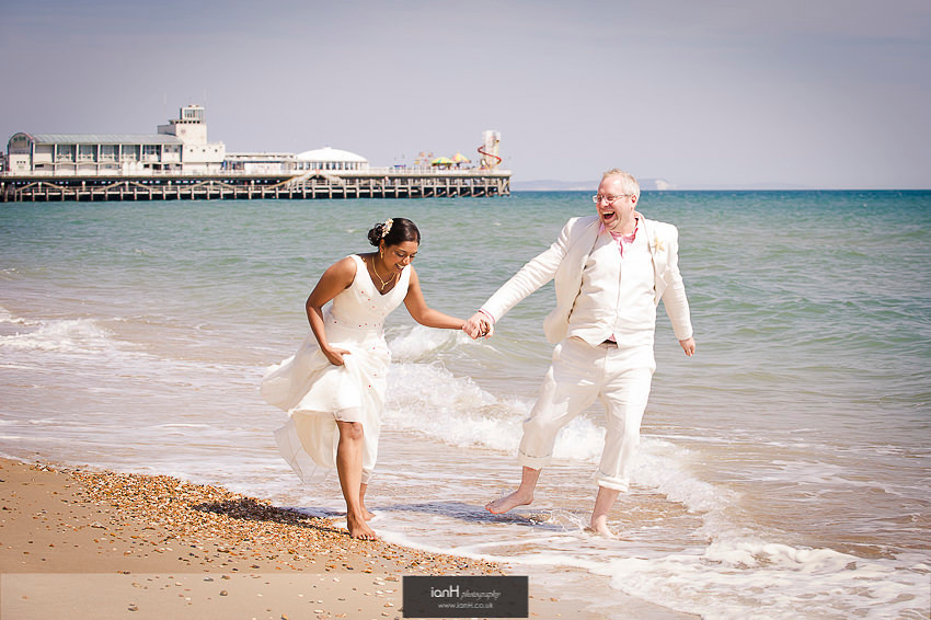 Bride and Groom layghing on Bournemouth beach