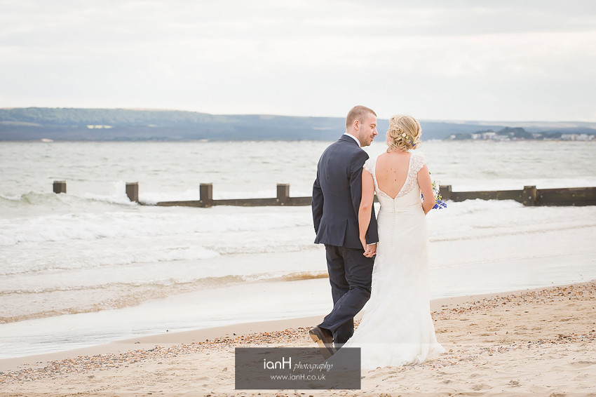 Bride and Groom walking hand in hand on Bournemouth beach