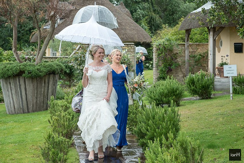 Bride under an umbrella leaving for the Church