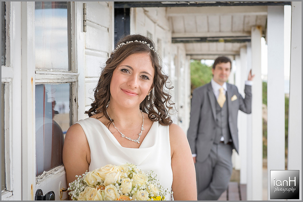 Bride and Groom smiling on the decking of beach huts in Bournemouth