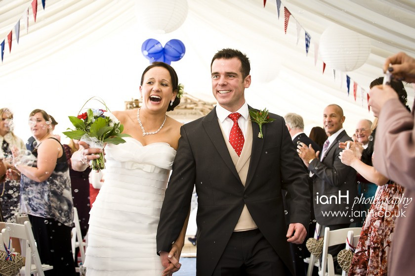 Bournemouth_beach_wedding_photographer_Bride_and_Groom_laughing_as_they_walk_up_the_aisle