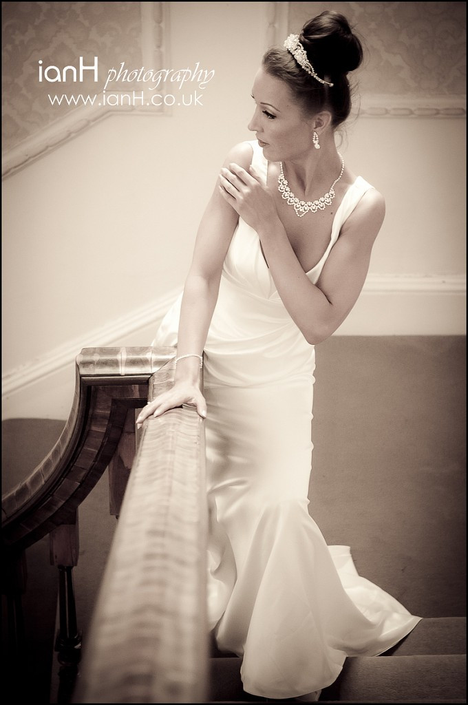 Bride_poses_on_a_stairwell_in_her_wedding_dress_at_Merley_House_in_Wimborne