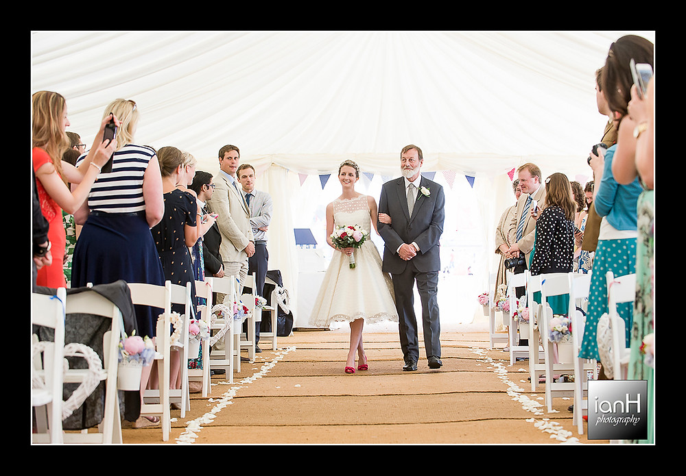 Beach Weddings Bournemouth - Sarah and Andy - a beaming Bride being walked down the aisle
