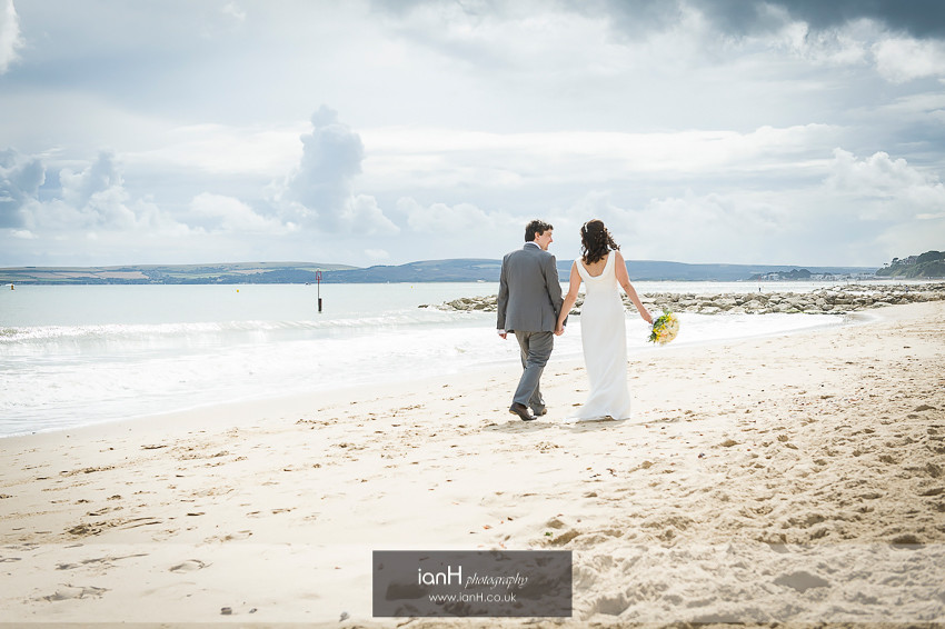Bride and Groom walk along Bournemouth beach