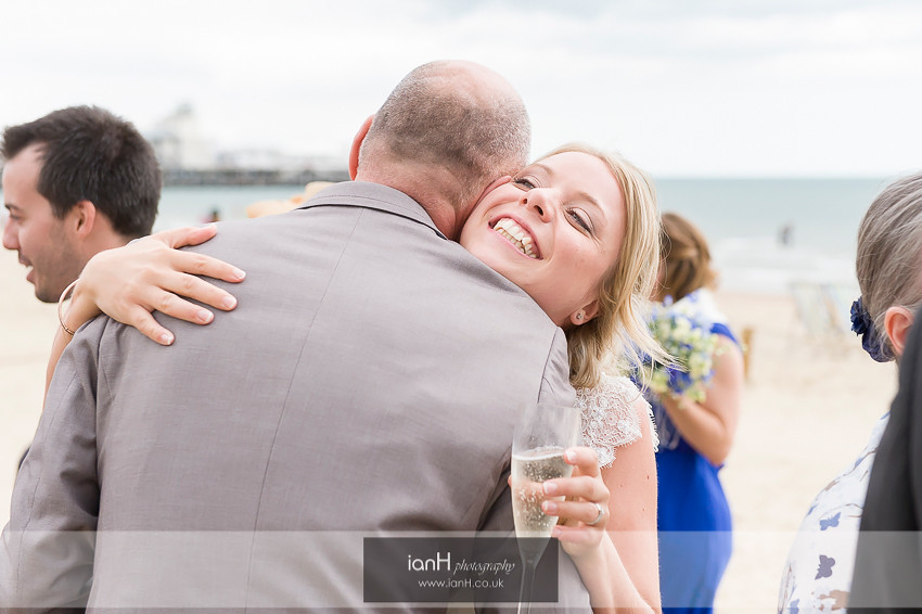 Smiling Bride hugs wedding guest on Bournemouth beach