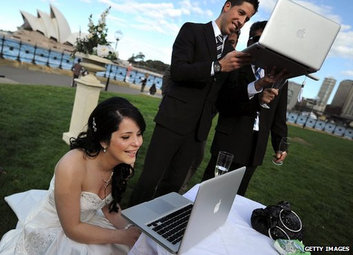 bride-and-groom-using-laptops-on-their-wedding-day