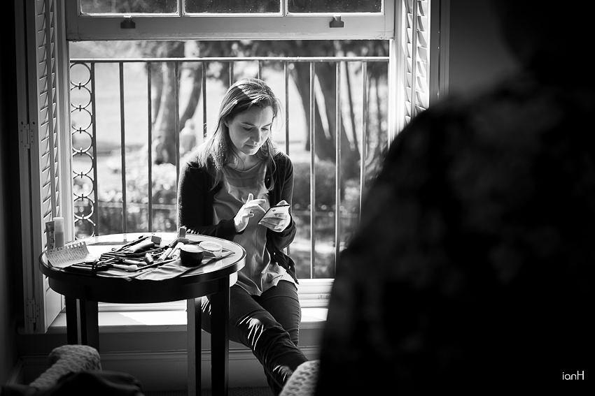 Bridesmaid checking her phone at Kings Arms Christchurch wedding