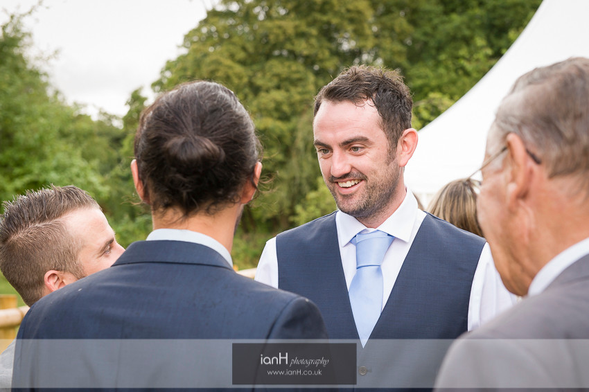 Groom with guests at Hampshire country marquee wedding
