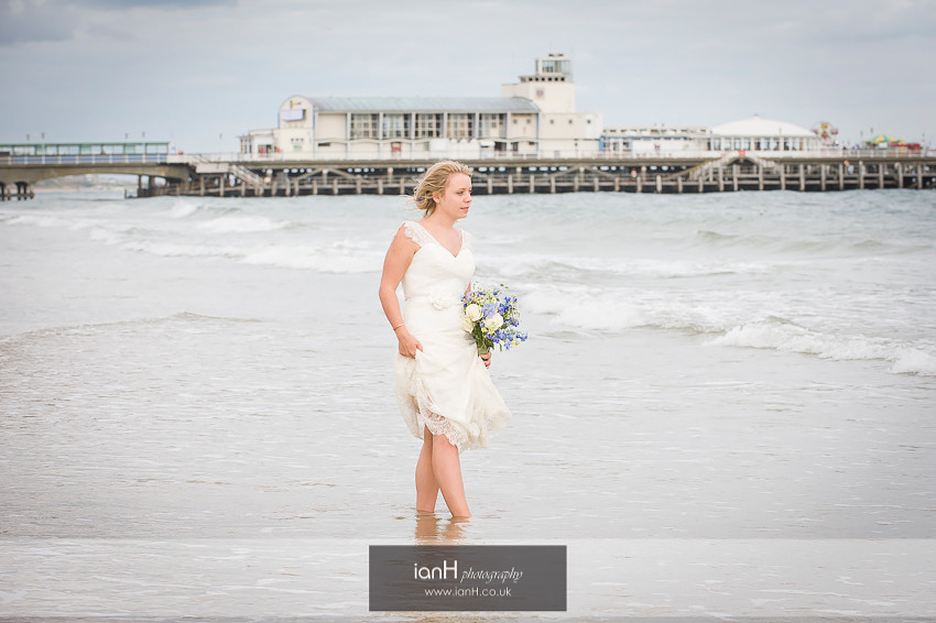 Bride paddling on Bournemouth beach with Pier in background