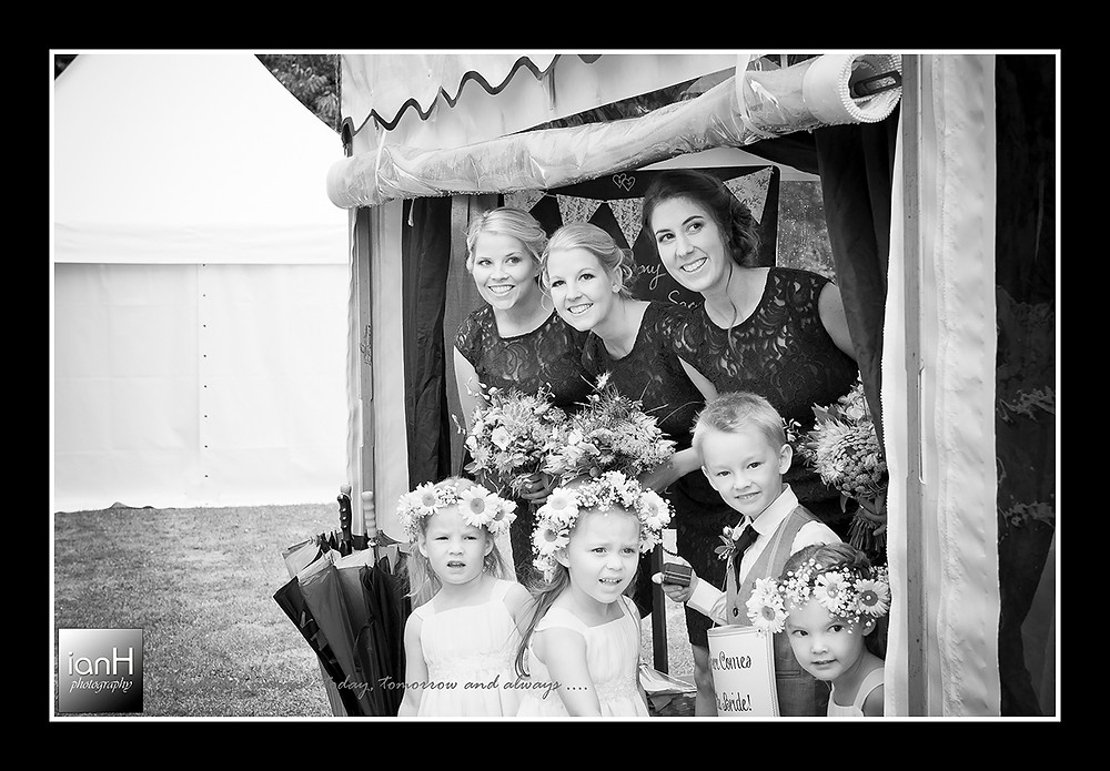 The bridesmaids and flowergirls shelter from the rain as they wait for the Bride