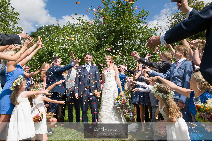 A shower of confetti falls on the Bride and Groom