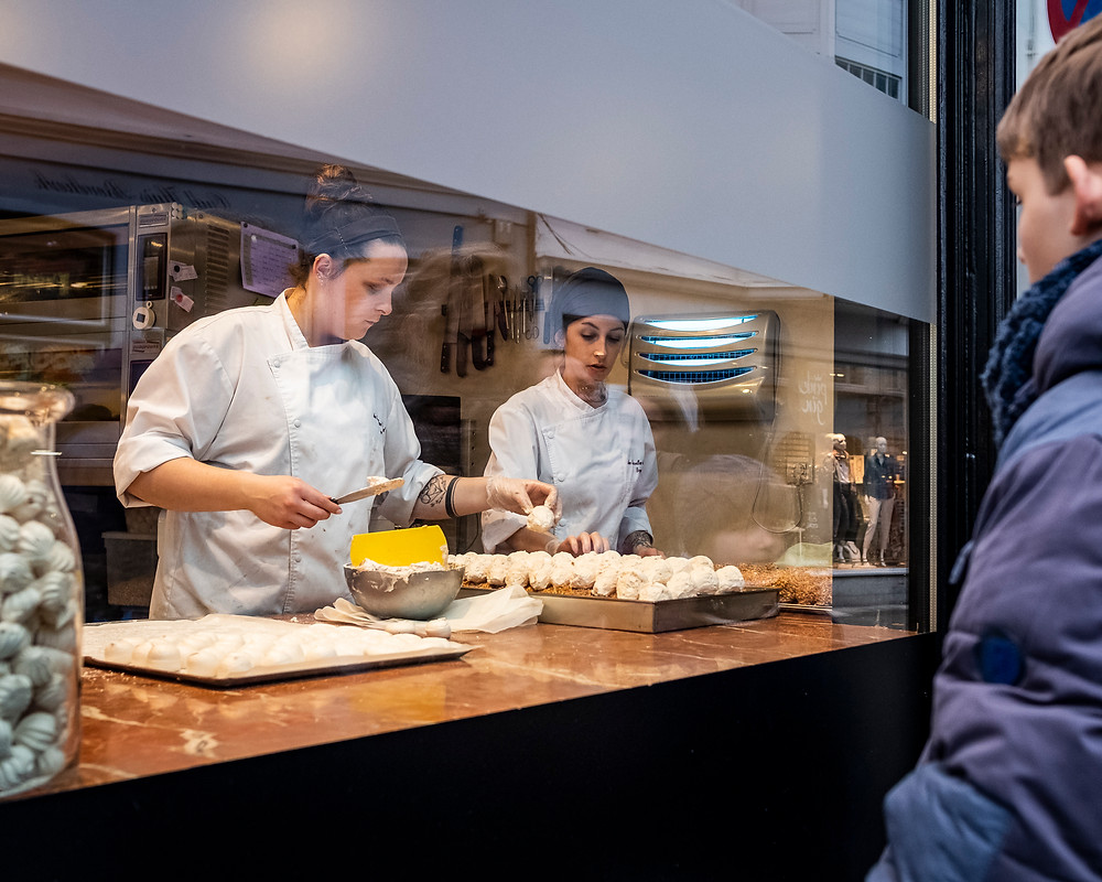 Small boys watching macrons being made in a restaurant in Bruges, Belgium