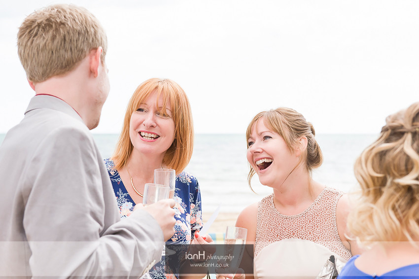 Wedding guests laughing on Bournemouth beach