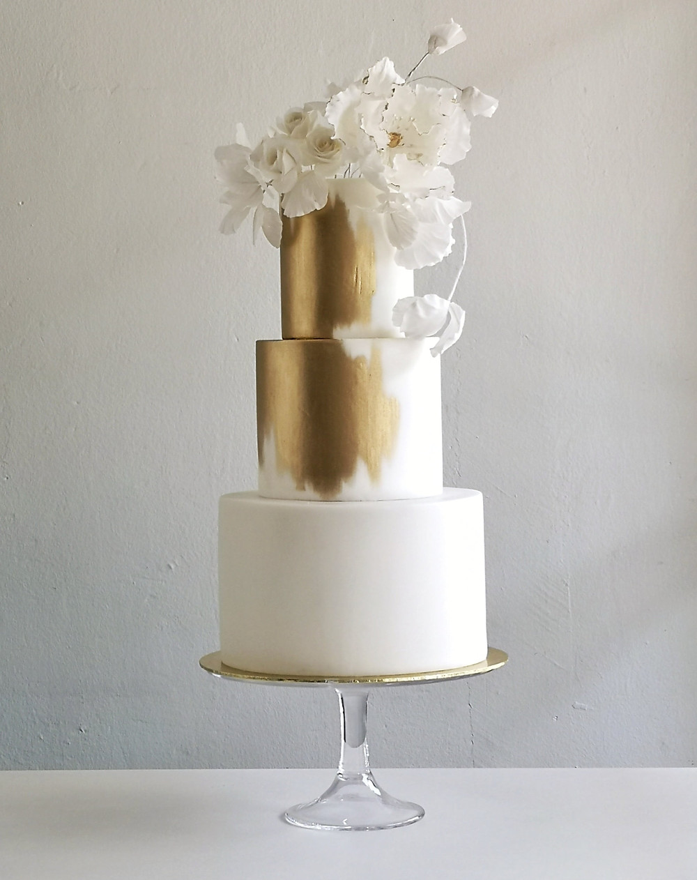3 Tier White Wedding Cake with a Splash of Gold and white flowers