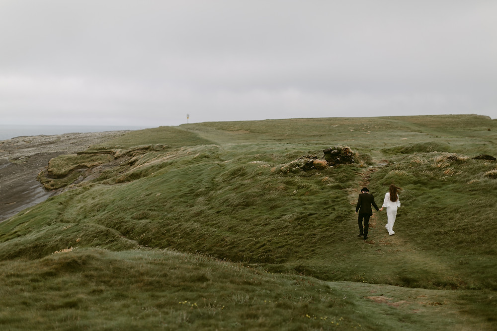 Destination Pre wedding Photoshoot: Couple walking across an unkempt landscape
