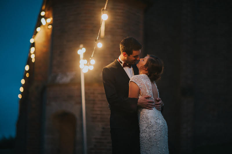 Wedding Photography: Groom and bride kissing at night ceremony under fairy lights