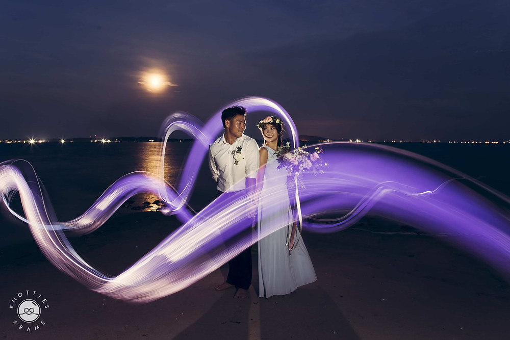 Night Wedding Photography: Couple backfacing each other with purple light surrounding them