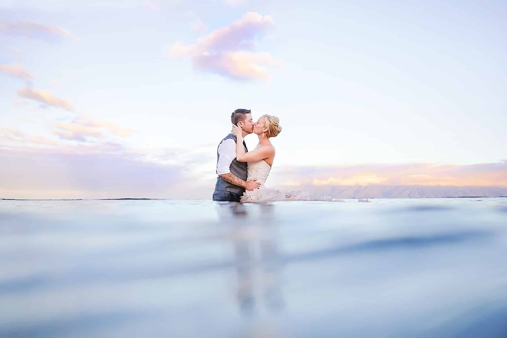 Pre Wedding Photoshoot: Couple in embrace and kissing waist deep in sea waters