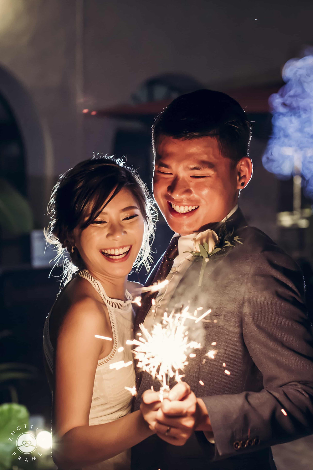 Night Wedding Photography: Couple holding sparklers and smiling