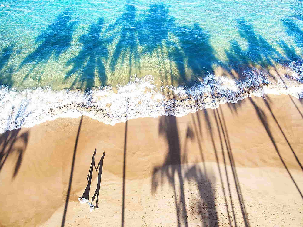 Pre Wedding Photoshoot: Aerial view of couple walking on the beach with shadows of palm trees