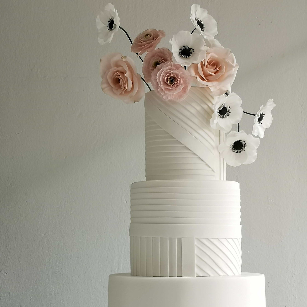 Minimalist White 3 Tier Wedding Cake with Sugar Flowers at the Top