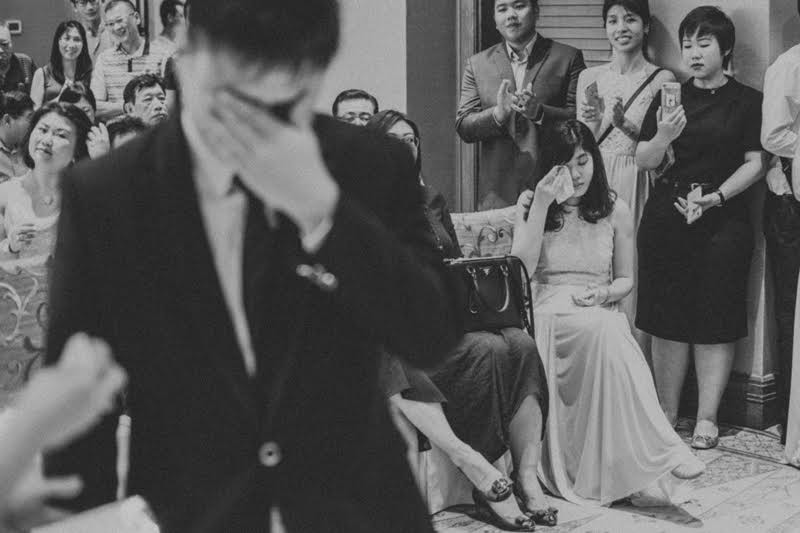 Wedding Photography: Emotional groom wiping tears with wedding guests in the background