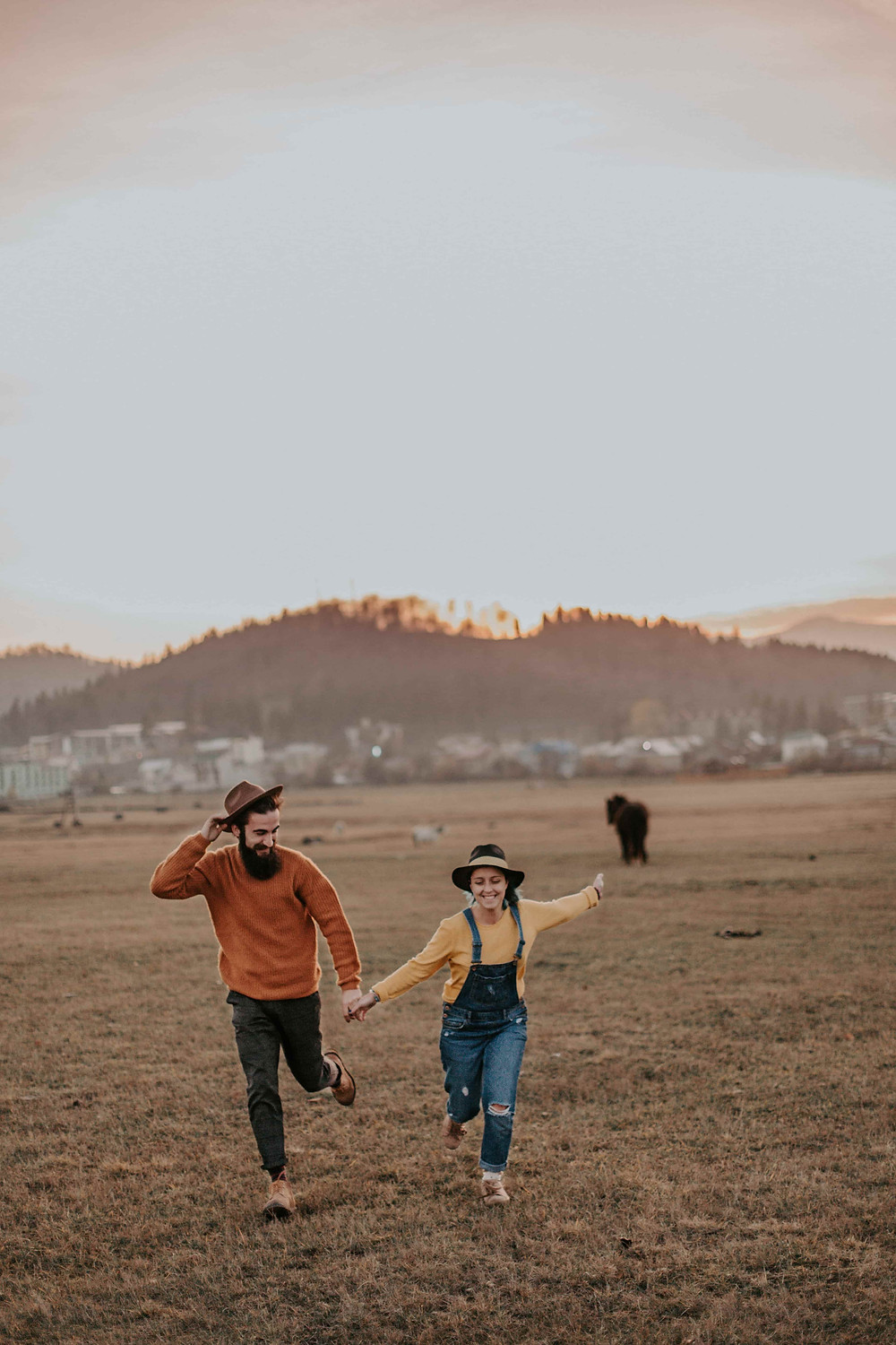 Wedding Shoot Pose Where Couple is holding hands and running through a field