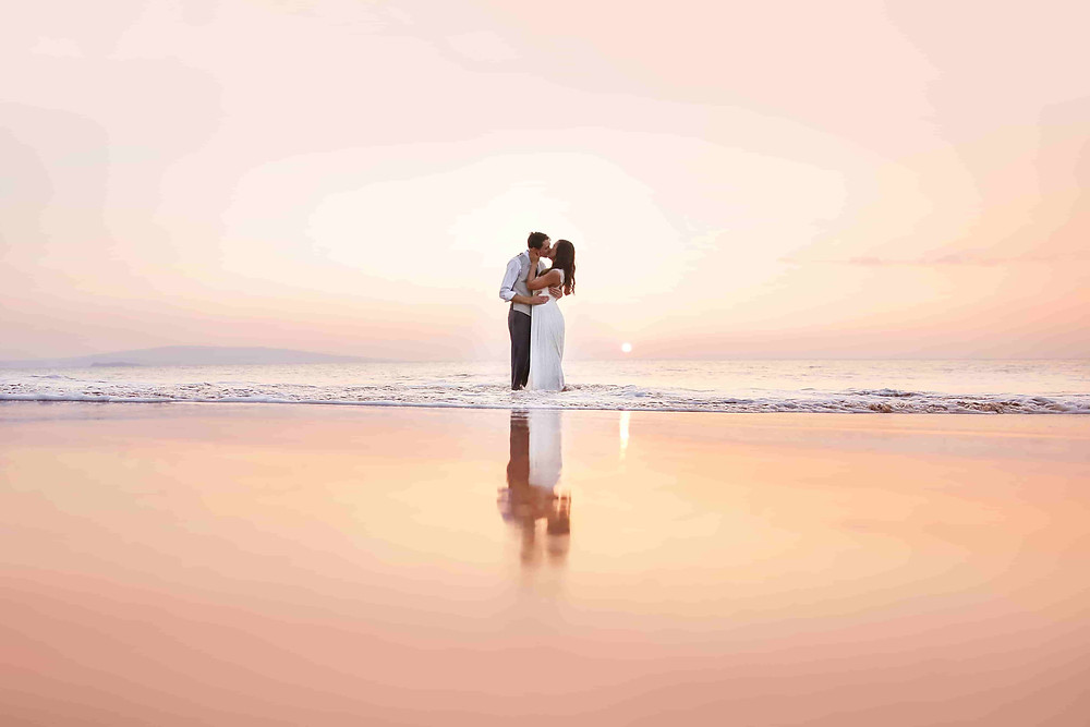 Pre Wedding Photoshoot: Couple in embrace on the beach with the sunrise behind