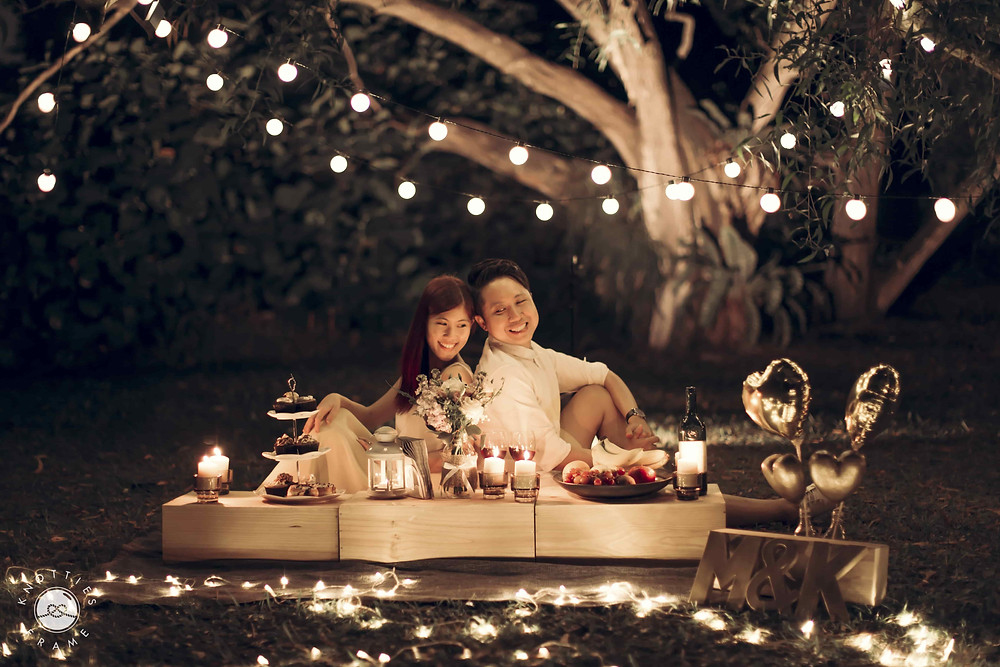 Night Wedding Photography: Couple surrounded by fairy lights around a picnic set up