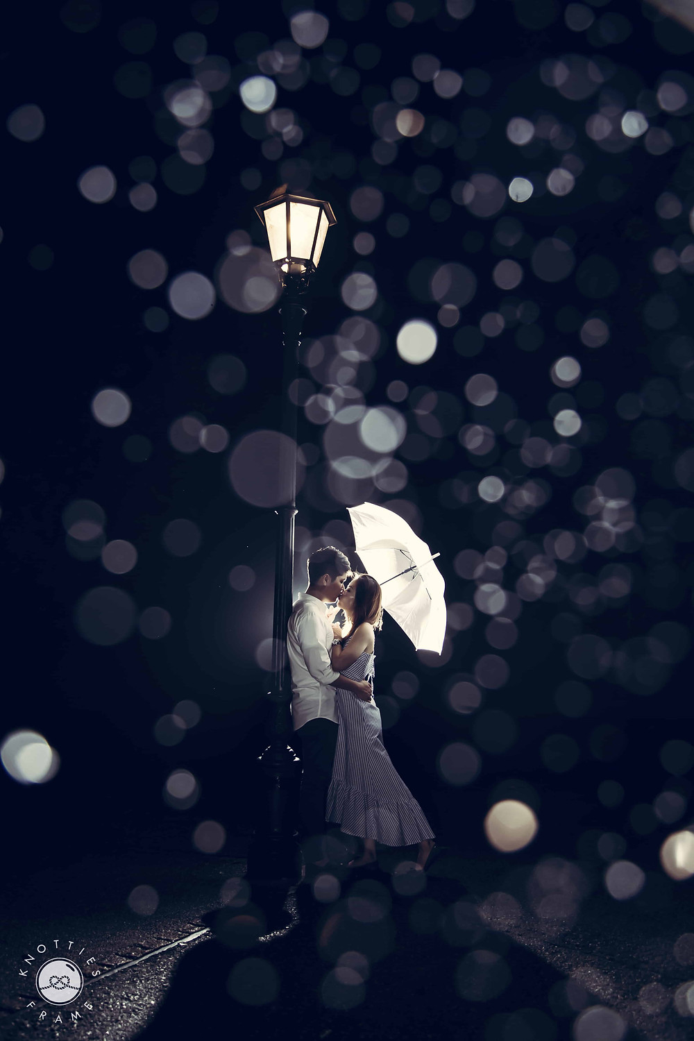 Night Wedding Photography: Couple standing under a lamp post in the rain holding umbrella