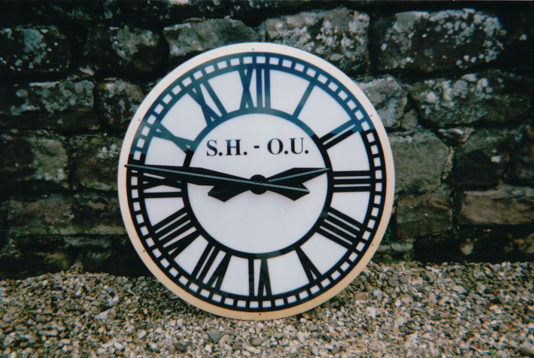Skeleton outdoor clock with gold rings and sign writing
