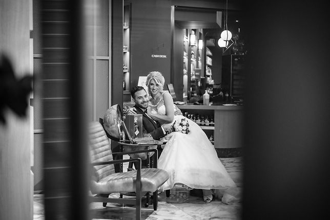 Wedding couple, Bride sitting on Groom's lap with flower bouquet in venue reception
