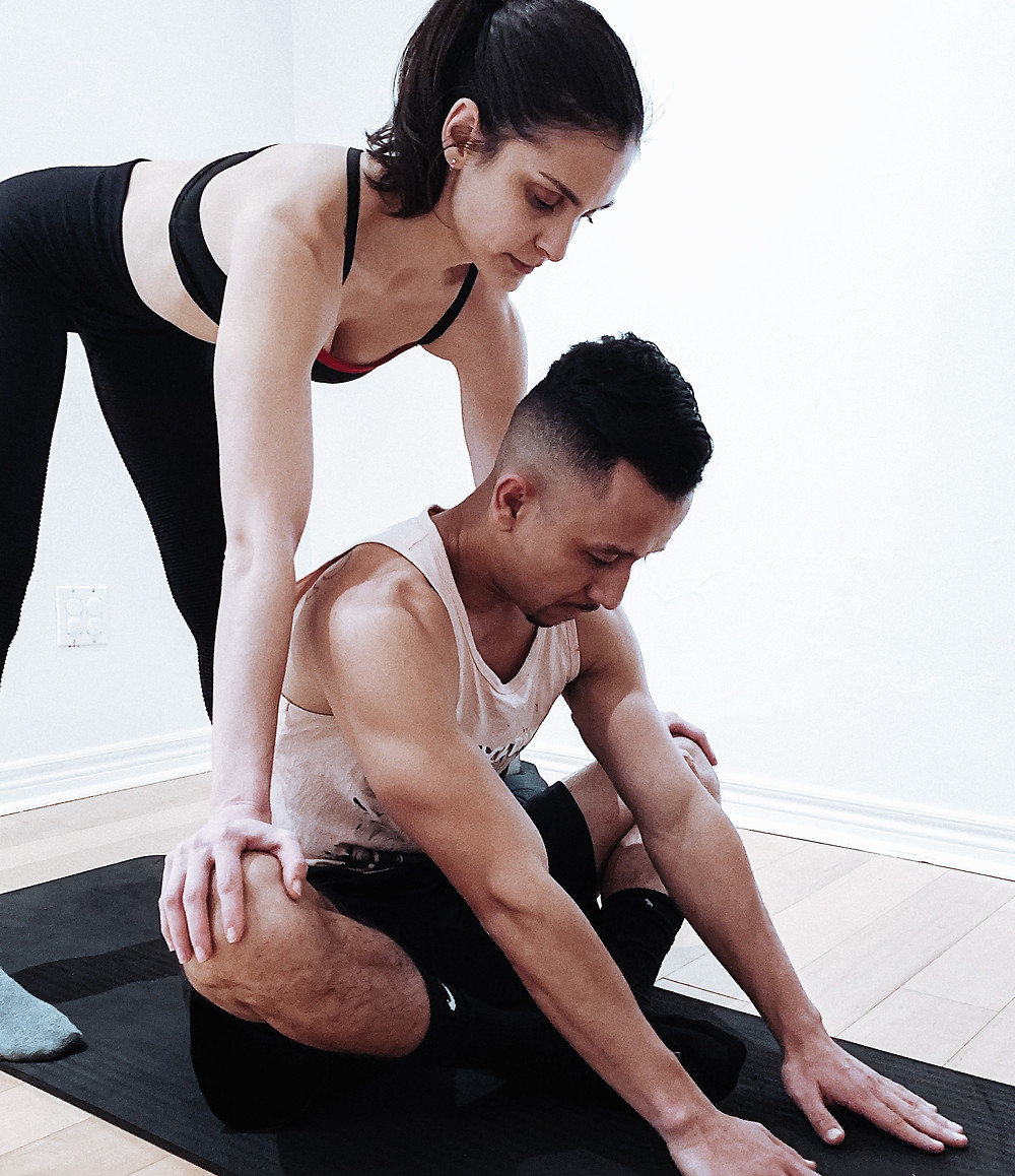 Jemma assisting her student during a stretching class
