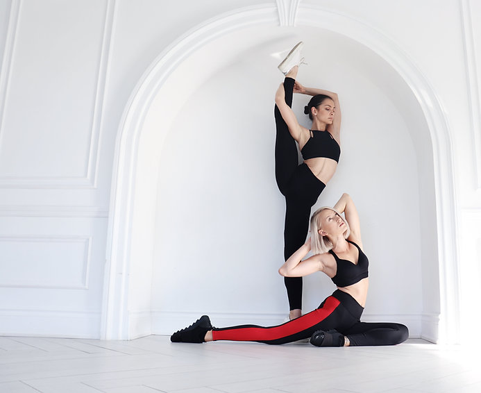 Zhana and Jemma Stretching Against a Wall
