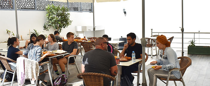 Arabic studens enjoying their lunch on the terrace on a sunny day