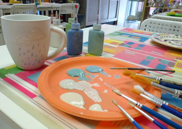 Brushes with paint and a mug