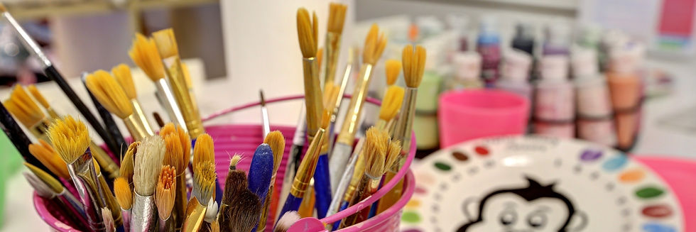 Paintbrushes in pot with underglaze pottery paints and colour plate