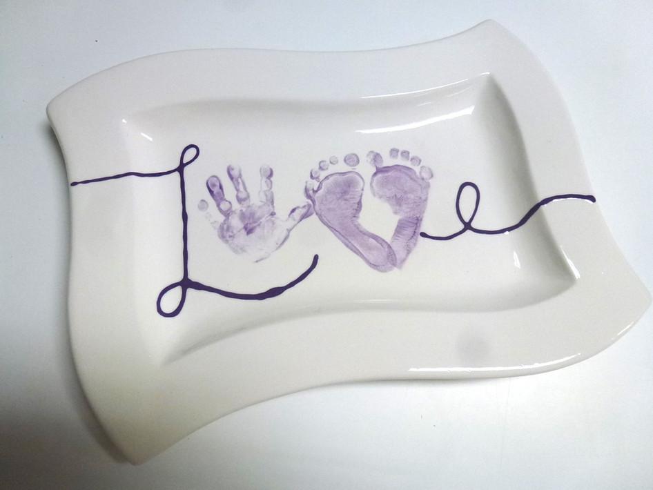 love written with handprint and footprint on platter