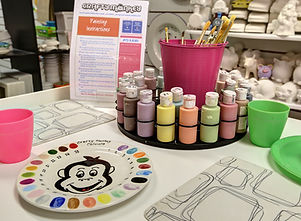 Table set up with paints, brushes for pottery painting