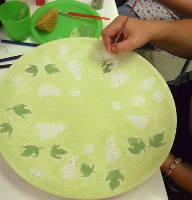 Painting a platter with grapes and vines