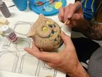 A man painting an owl tealight holder