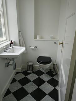 Selvom et gæstetoilet er småt, kan det godt spille sammen med et eksklusivt hjem. Sort og hvid Carrera marmor i klassisk skaktern.
