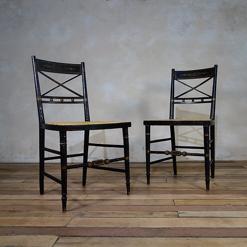 A Pair Of Regency Ebonised and Caned Side Chairs
