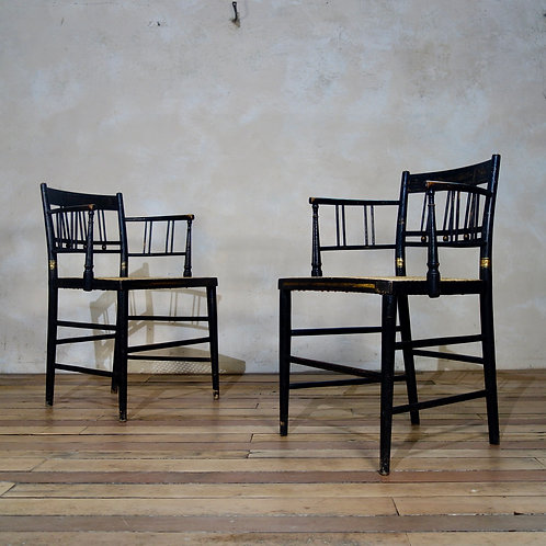 A Pair Of Regency Ebonised and Caned Armchairs